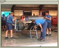 看 the team working in the garage to prepare the car for the race.
