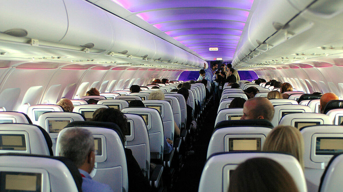 Passengers enjoy Virgin America's in-flight entertainment system, which includes on-demand movies, television, video games, music and onboard chat rooms during a flight from New York to San Francisco. Bob Riha/WireImage/Getty Images