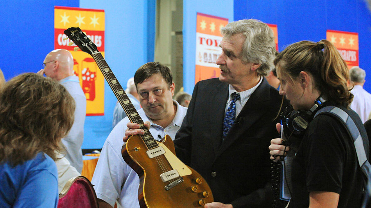 Richard Johnston, musical instruments appraiser for 'Antiques Roadshow' holds a 1955 Les Paul guitar brought for appraisal by Dan Sillaman (white shirt in background). Sillaman and his guitar were selected to be filmed for a later airing of the show.  Tracy A Woodward/The Washington Post via Getty Images