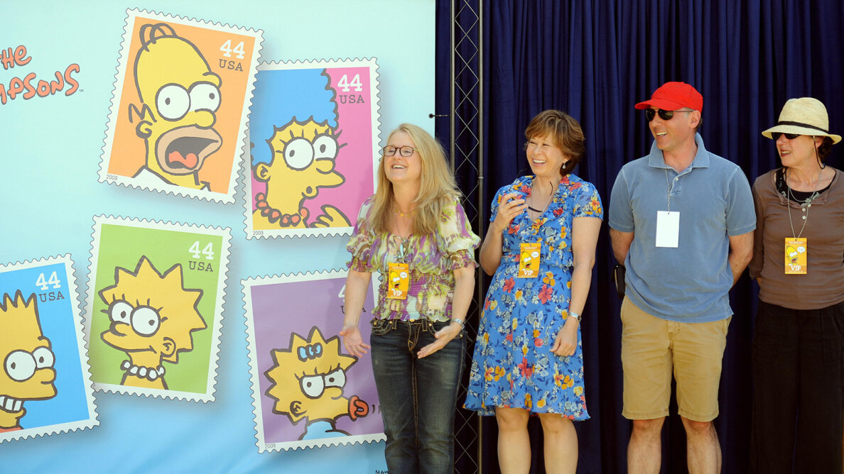 Nancy Cartwright, Yeardley Smith, dan Castellaneta and Julie Kavner (L-R), voice actors on the show, pose by stamps featuring Simpsons characters. GABRIEL BOUYS/AFP/Getty Images