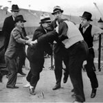 "Ford Service Department members assault union organizer Richard Frankensteen during the ""Battle of the Overpass"" in 1937."