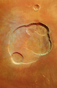 "The top of Olympus Mons is pictured above. This is the largest mountain in our solar system. It is an extinct volcano that is more than three times taller than Mount Everest. The depressions in this picture are called ""caldera pits."""