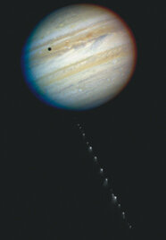 """This image shows the pieces of Comet Shoemaker-Levy 9, nicknamed """"a string of pearls."""" The dark spot at the top left of Jupiter is the shadow of Io, one of its moons."""