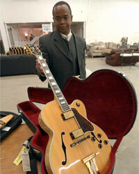 Mark Green with the IRS holds a guitar owned by singer Peabo Bryson in 2003. Much of Bryson's things were being auctioned off to pay a tax debt.­