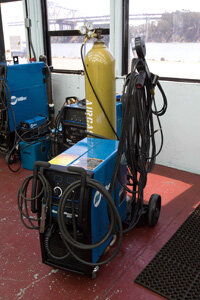 You can see the gas canister on the cart behind this Miller welder, that's one of the key components of MIG welding.
