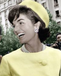 During her 1961 official visit to Paris, Jacqueline Kennedy sported an Alaskine (wool and silk) suit created by Oleg Cassini and pillbox hat created by Roy Halston Frowick.