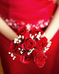 Bridesmaids in rich red gowns with velvety red roses make a big visual impact.