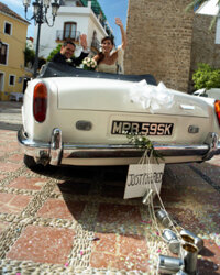 The bride and groom prepare to drive off for their honeymoon.