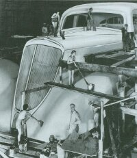 A retouched publicity photo of Studebaker's World's Fair car intersperses models with craftsmen at work.