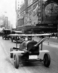 A car with wings and a propeller protruding from the radiator grille drives through Times Square, New York. This car was the invention of A.H. Russell of Nutley, New Jersey.