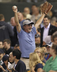 Sometimes, the action at a sporting event happens in the crowd. This Seattle Mariners fan celebrates after catching a fly ball.