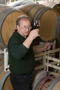 A professional winemaker uses a wine thief to sample a glass straight from the cask.