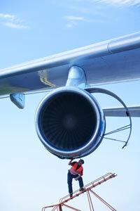 A flight mechanic attends to a modern gas turbine engine.