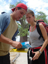 Rob and Amber pause to read a route marker while making their way to Botswana.