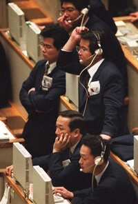 Traders react to a sell-off on the Tokyo Stock Exchange. Shares plunged partly because of arbitrage selling.