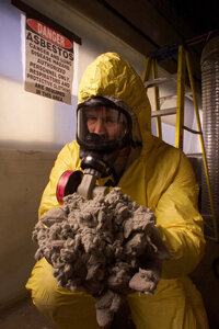 Asbestos Control Inc.'s Edward Zalig holds a pile of asbestos cleaned out from pipe insulation in Elk Grove Village, Ill.