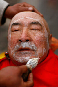 A barber shaves a man at his street-side stand on Feb. 24, 2009, in China. A haircut and shave can be had by a street barber for only 3 to 4 yuan (about 43 to 58 cents).