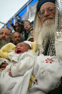 Rabbi Mordechi Eliyaho holds eight-day-old Adam as he and others participate in a circumcision ceremony during a sit-in in front of the Knesset.