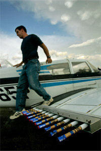 A pilot exits his plane past flares used in cloud seeding after flying a 2007 mission for the Western Kansas Weather Modification program.