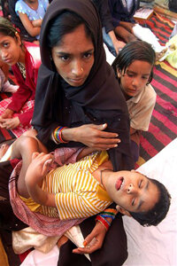 In 2007, a Bhopal resident carries her 10-year-old sister born with congenital abnormalities linked to the disaster.