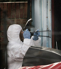 A forensic photographer takes a close-up image of a container's door in Bexley, England. Police had just discovered millions of pounds stolen in a bank heist.