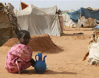 A young girl washes plates in the North Darfur refugee camp of El Sallam on Oct. 4, 2006.