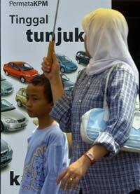A woman and her son walk past a bank's car loan poster in Jakarta.