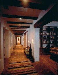 This hallway offers a sitting place, windows, and ambiance.