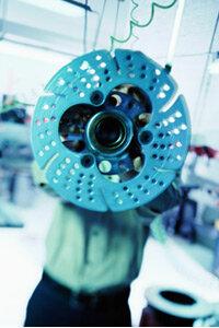 Mechanic holding brake disc.
