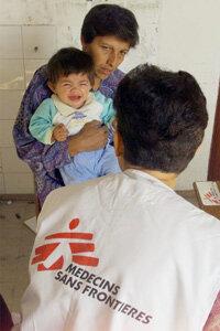 A doctor examining a baby in Kosovo.