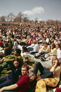 Crowds of people celebrate Earth Day 1970 in a park.