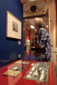 "A visitor tries to get a closer look at an Escher lithograph at The Hague's ""Escher in the Palace"" exhibit."