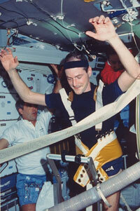 Astronaut G. David Low using a treadmill aboard the space shuttle Columbia as fellow crewmembers Daniel C. Brandenstein and James D. Wetherbee look on.