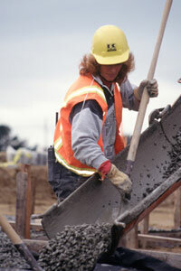 A worker pours concrete into formwork using a hose.