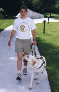 An instructor and a future guide dog practice walking on the Guiding Eyes for the Blind training grounds.