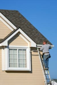 A workman fits a piece of extruded aluminum to the roof line of a house in Missouri.