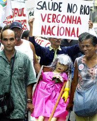 "A protestor holds a sign reading ""Public Health in Rio, National Shame"" at a 2005 protest in Brazil."