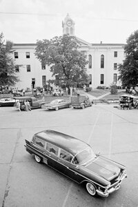 The hearse bearing the body of novelist William Faulkner passes the Lafayette County Courthouse in Oxford, Miss., July 7, 1962.­