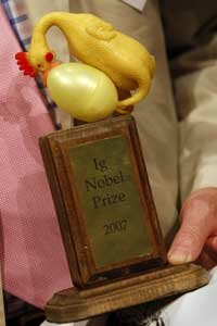 A proud (or at least tolerant) recipient brandishes a 2007 Ig Nobel Prize.