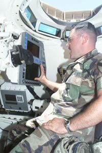 A tank gunner examines the commander's display unit on the M1A2.