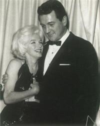 Marilyn hugs the Golden Globe award she received in early 1962; with her is Rock Hudson.