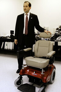 U.S. Attorney Alex Acosta shows a wheelchair that was used in a case of Medicare fraud worth more than $2.8 million in 2006. Patients would sit in the chair to prove they needed it, then submit a photo of that to Medicare.
