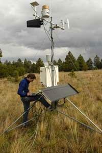 A scientist checks local conditions at a weather station in Arizona.