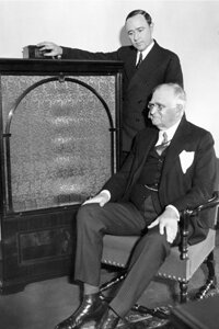 Merlin H. Aylesworth (standing), President of NBC, and Paul D. Cravath (sitting), President of the Metropolitan Opera Company, listening to the opera on the radio after making their introductory remarks on Christmas Day in 1931.