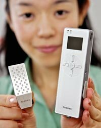 Toshiba employee Hiroko Mochida displays an MP3 player along with a prototype model of a direct methanol fuel cell (DMFC).