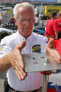 NASCAR official George Metrick examines a restrictor plate during a pre-race inspection for qualifying.