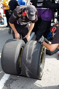 Crew members check the tire wear after a pit stop during a NASCAR Sprint Cup Series race.
