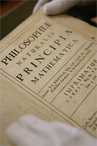 A very excited librarian holds a copy of one of the most important scientific works ever written, the Principia.