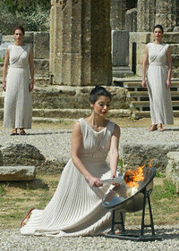 Actress Thaleia Prokopiou ignites the Olympic Flame with the use of a parabolic mirror during a Torch Lighting practice session outside the Temple of Hera in Ancient Olympia, 2004.