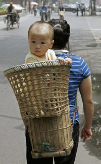 A mother caries her baby in Beijing.
